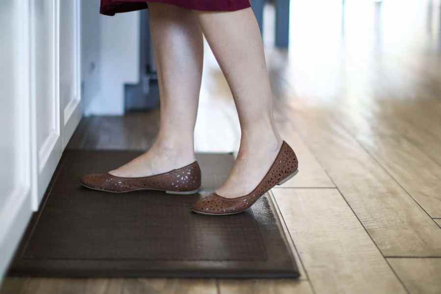 Woman using an anti fatigue mat in the kitchen